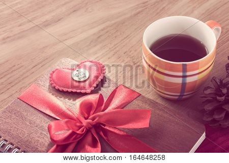 notebook wrapped with red ribbon red felt hearts in vintage pink color tone with cup of coffee all on wooden table good for valentine or special occasion