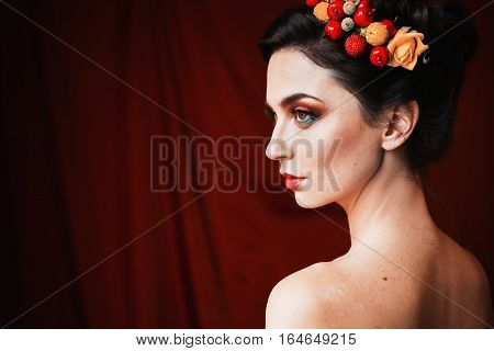 a beautiful girl brunette woman with brown eyes with bright makeup make-up with berries and flowers in hair red lips unusual appearance a woman with tanned skin on red dark background profile