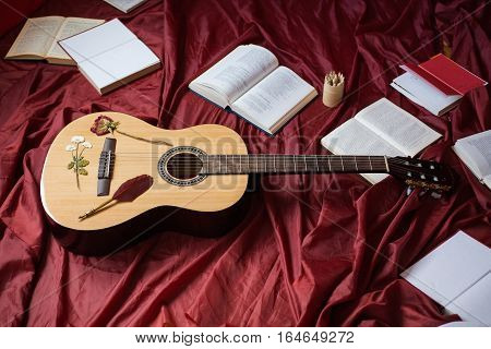 Guitar lying on red fabric dried flowers books on a red background scattered books fountain pen art atmosphere