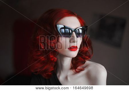 red-haired girl with red lips and pale skin with dark glasses on a dark background reflection glasses stylish woman red curly hair bright make-up