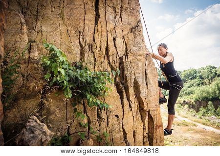 Young climber rock climbing in a an old quarry.