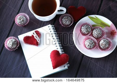 chocolate balls on the plate, mini marshmallows, red felted heart, heart shaped bookmark and notebook on purple wooden background Valentines day background top view place for text