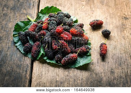 Mulberry On Leaf With Wooden Background