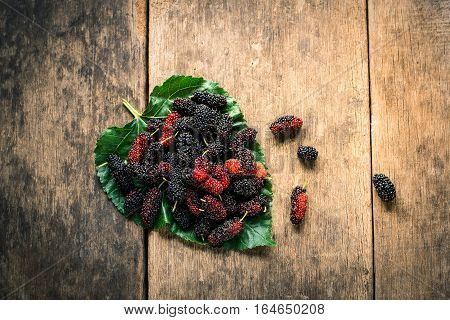 mulberry on leaf with the wooden background