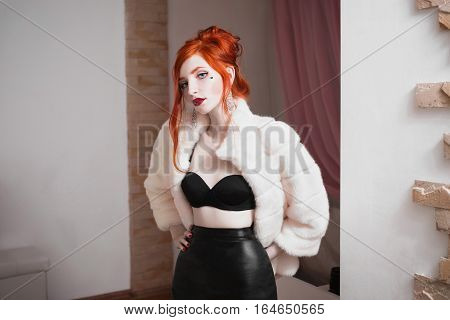red-haired girl with blue eyes and red lips in luxurious white fur coat and black skirtwoman with earrings and a heart on her cheek luxurious femme fatalewoman vulgar girl with an interesting appearance red hair