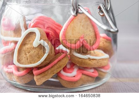 a glass Jar with homemade heart shaped cookies on light background