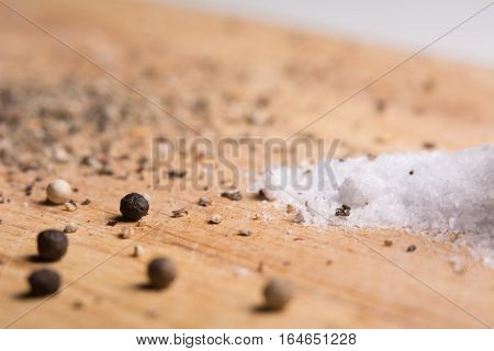 Pepper And Salt On A Kitchen Wooden Board.