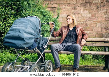 Young father enjoying time outdoors, taking their baby to a park along the banks of the river Neckar in Heidelberg, Germany.