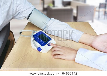 Concept of female doctor press start button on blood pressure or sphygmomanometer in blur clinic background