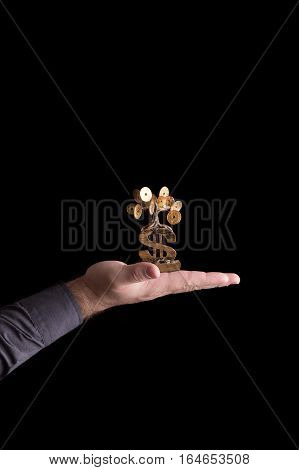 A man holding a money tree in hand on a black background