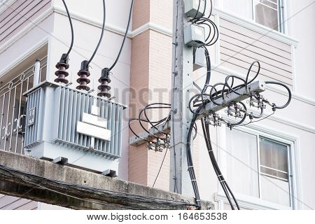 High voltage electrical transformer high on concrete poles House background