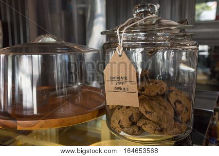Chocolate chip soft cookies in a glass jar in coffee shop and bakery