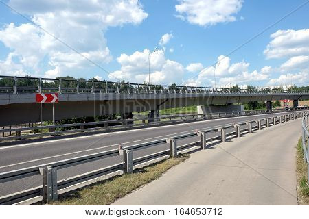 Cityscape with empty urban highway, overhead road and pedestrian way with fence in sunny summer day horizontal photo side view closeup