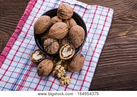Walnut kernels and whole walnuts on old wooden table and dish towel