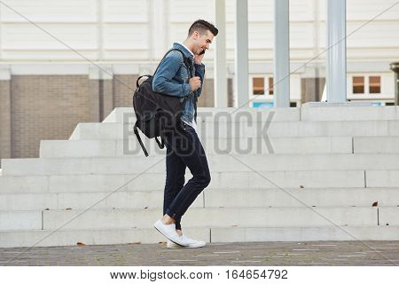 Smiling Young Man Walking And Talking On Cellphone Outdoors