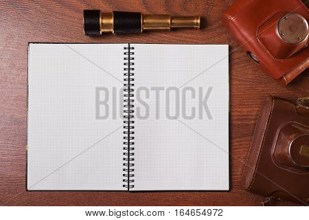 a sheet of paper from a notebook spyglass and case for the camera on wooden background copyspace