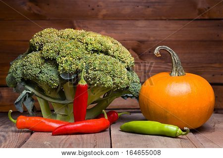 Fresh healthy useful vegetables broccoli, pumpkin, peppers on wooden table close up. Purple tinted