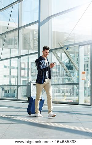 Happy Man Walking With Suitcase And Phone In Terminal