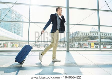 Smiling Man Walking In Station With Telephone And Suitcase