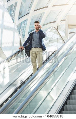 Portrait of serious business man standing on escalator on mobile phone