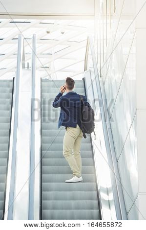 Business Man From Behind Standing On Escalator On Phone Call