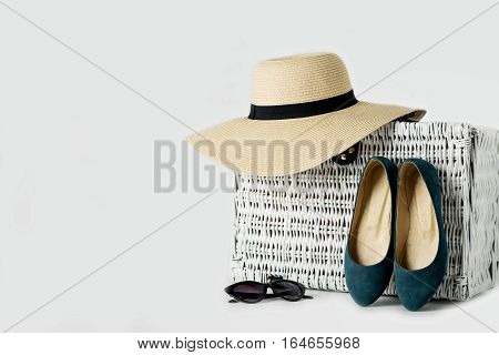 White wicker suitcase women's hat glasses and blue shoes.