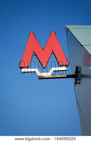 Sign indicating entrance to the Moscow metro station over blue cloudless sky vertical front view closeup