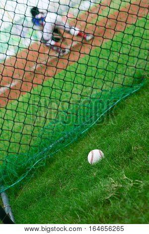 baseball outside of a baseball field with catcher at background selective focus