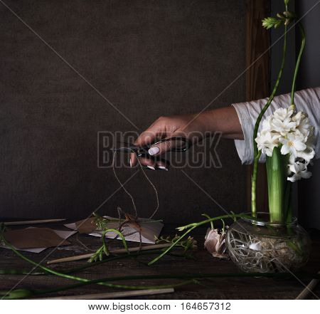 three white hyacinth in transparent vases, a female hand with scissors on dark background.
