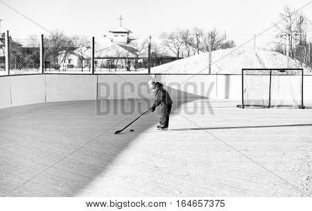Four year old toddler girl on skates at an outdoor ice skating rink learning to play hockey with stick and puck in black and white