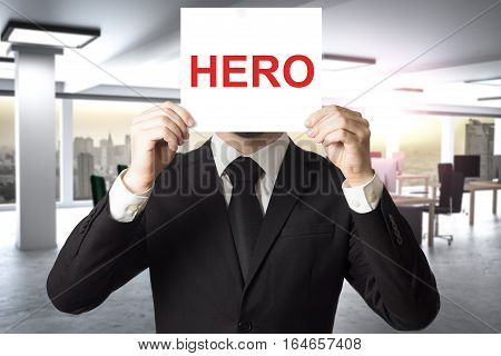 businessman in modern office hiding face behind sign hero