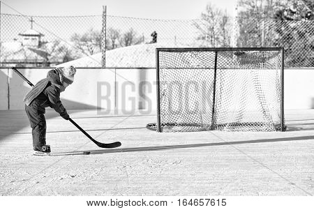 A four year old toddler girl on skates trying to shoot the puck into the net on an outdoor ice skating rink in black and white