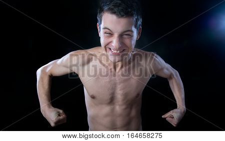 skinny young man making muscle against black background
