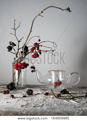 still life. viburnum branches with berries and snow in a transparent vase, glass teapot on a wooden table