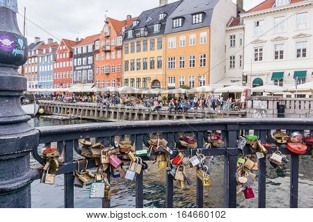 Copenhagen, Denmark, July 10, 2016 - Padlocks attached to the railing of a bridge over the canal in Copenhagen harbour. The locks have different inscriptions and the keys were thrown into the water.
