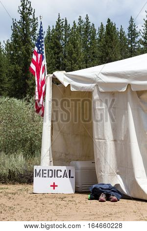 Medical tent entrance with a hand-made medical sign and an American Flag. Runners aid station as indicated by the shoes outside of the entrance.