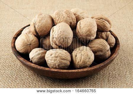 Walnuts on a wooden plate and a burlap cloth in natural colors close-up.