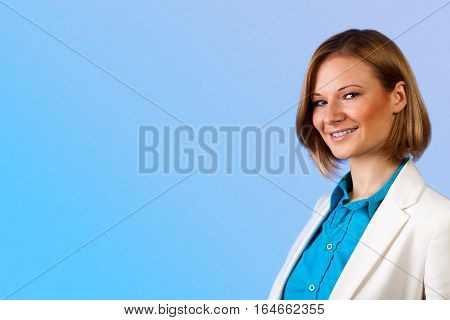 Studio portrait of a young beautiful businesswoman in a blue shirt and beige jacket