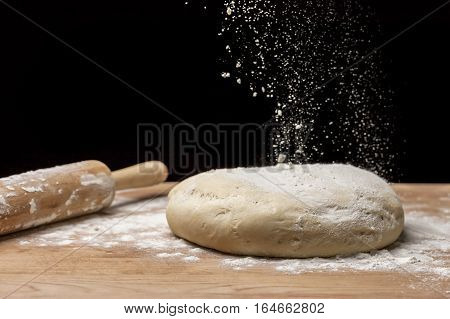 Close up of flour sprinkled on a clump of dough on a flour covered board.
