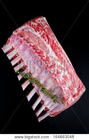 Fresh Raw French whole rack of pork loin with ribs on black board