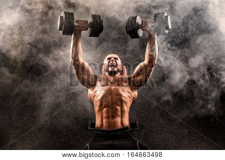 Bald Topless Muscular Man Doing Exercises With Two Dumbbells On Bench Press In Smoke