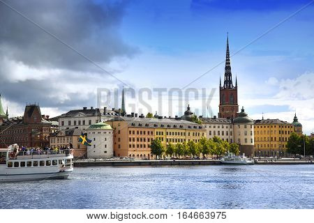STOCKHOLM SWEDEN - AUGUST 19 2016: Tourists boat and View of Gamla Stan from Stockholm City Hall ( Stadshuset ) in Stockholm Sweden on August 19 2016.