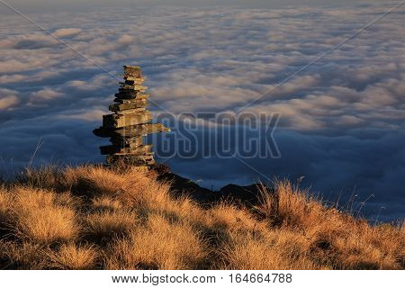 Autumn scene in the Annapurna Conservation Area Nepal. Cairn and sea of fog.