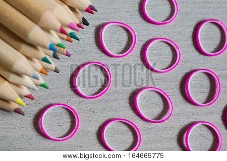 colored pencils colored rubber bands on wooden background conceptual idea