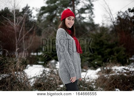 Girl in red hat and scarf walking in winter park. She smiles and very pleased and happy.
