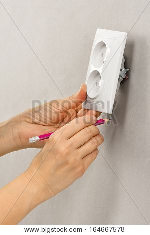 hand with pencil showing where will be wall electrical socket during repair