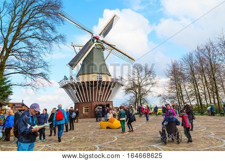 Lisse, Netherlands - April 4, 2016: Traditional dutch windmill and tourists in the spring Keukenhof garden