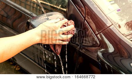 Washing a car by yourself Microfiber cloth for cleaning a wing mirror