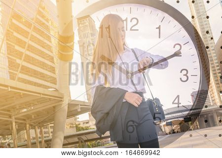 Double Exposure of Business Woman Looking at Watch in Modern City and Clock as Time management concept