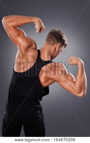 Handsome Muscular Man Posing On The Gray Background. Concept Of Healthy Lifestyle